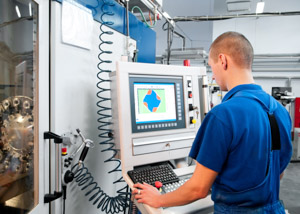 student with machinery and computer screen